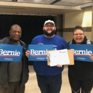 Three Iowa caucus goers hold signs for Bernie Sanders and a CCI petition
